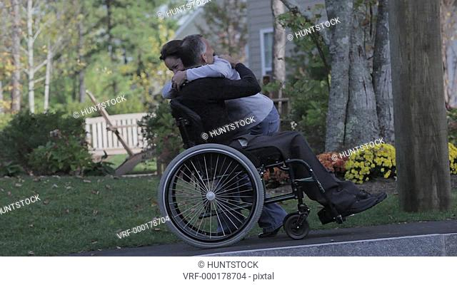 Man with spinal cord injury in a wheelchair hugging his wife