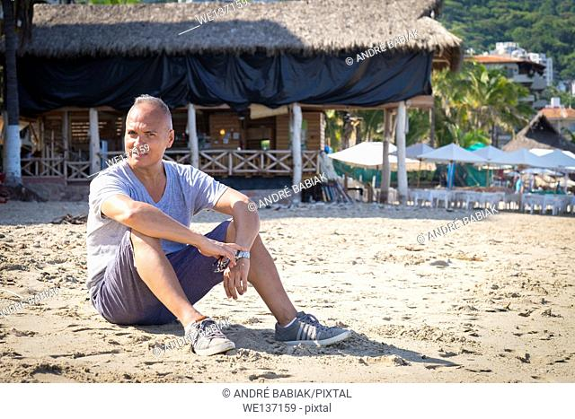 Tourist in Puerto Vallarta, Mexico. Man, 55 years old, hispanic ethnicity, sitting in the sand. Palapa restaurant in the background
