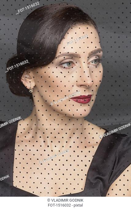 Close-up of beautiful woman seen through net