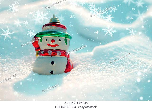 Winter concept with snowman and snowflakes on snow background