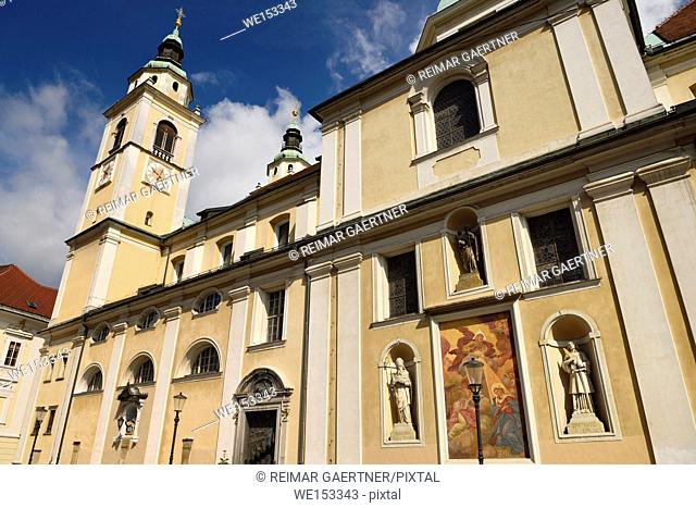 Southern facade of St. Nicholas church Ljubljana Cathedral Slovenia with belfry, frescoe, and statues of saints Joseph, Hermagoras and Fortunatus