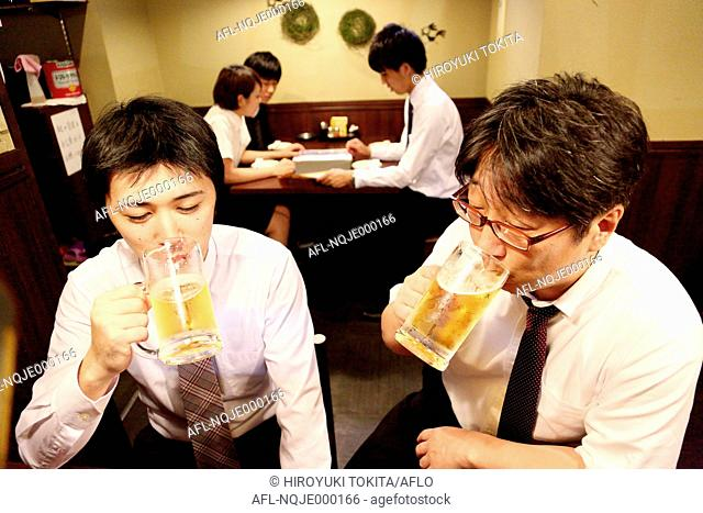 Japanese businessman drinking with his boss at a Japanese style Izakaya