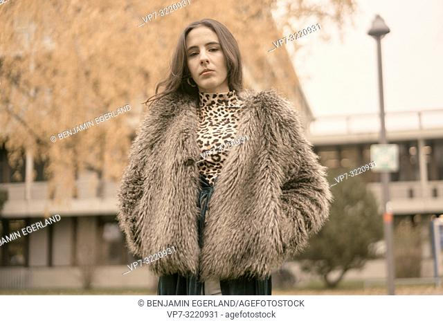 confident woman standing outdoors in city park, autumn season, individual fashionable style, in Munich, Germany