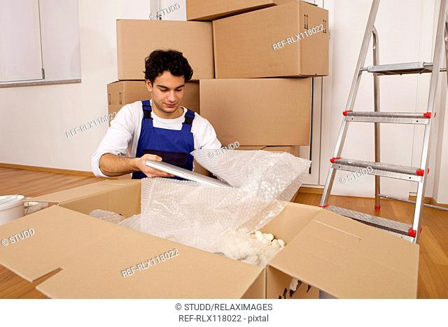 man young new home unpacking moving in boxes
