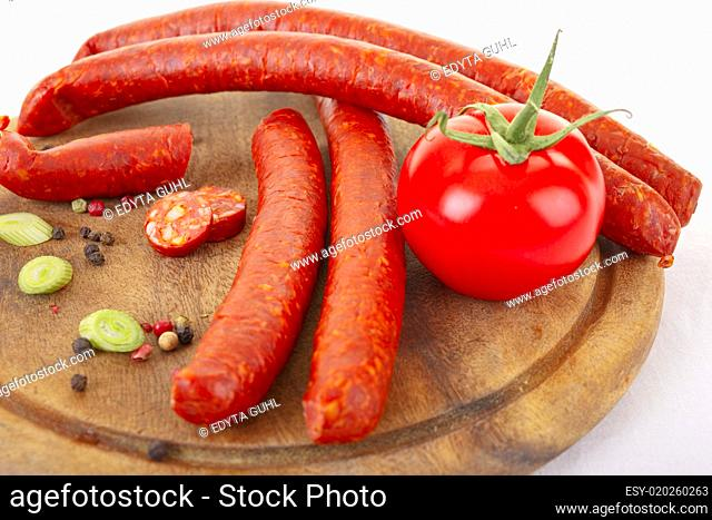 Spicy sausages and fresh tomato on wooden cutting bord