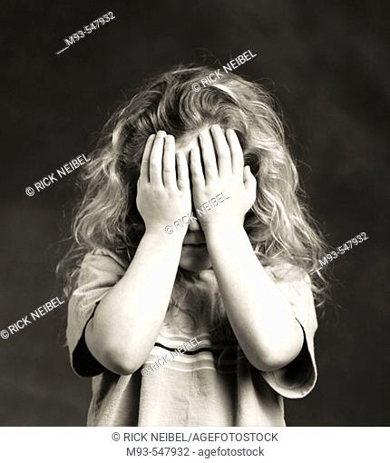 Black and white of young Caucasian girl approx. 6 years hold holding hands up to her face to cover her eyes