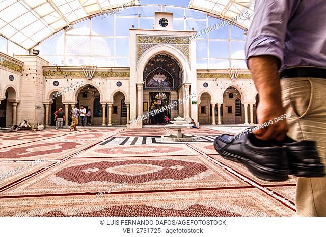Man carrying his shoes in the hand through the carpeted courtyard of the Sayyida Ruqayya mosque in Damascus, Syria