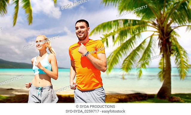 smiling couple running over tropical beach