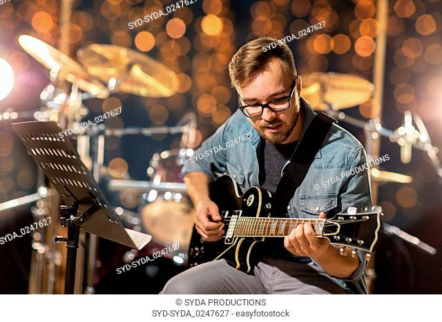 musician playing guitar at studio or music concert