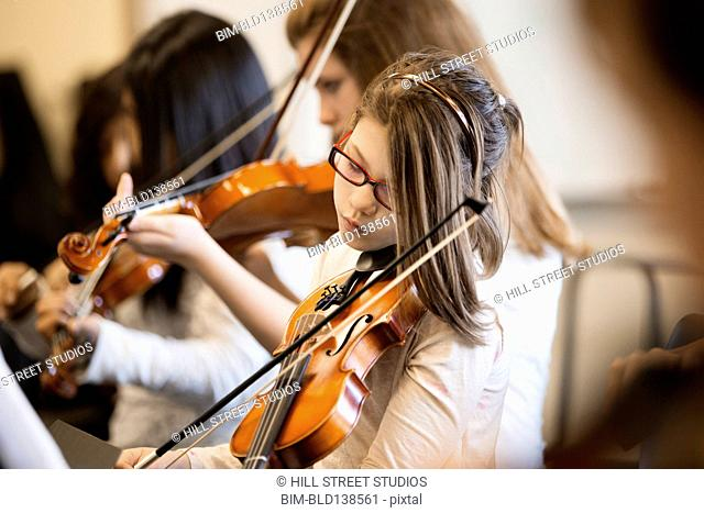 Caucasian girl playing violin in music class