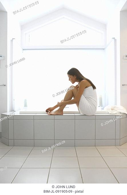 Woman wrapped in towel painting toenails on side of tub