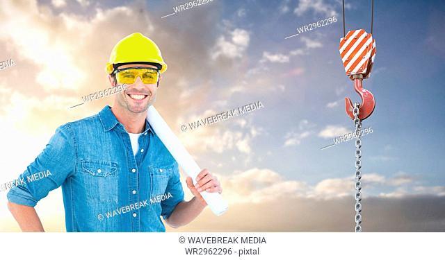 Smiling architect holding blueprints by crane hook