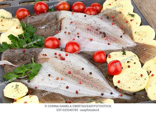 Baking tray with raw turbot fish and sliced potatoes, seasoned with black and red pepper, cherry tomatoes and parsley, ready to be baked