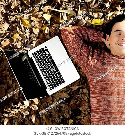 Man with a laptop lying on autumnal leaves