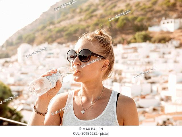Woman drinking water on viewing platform overlooking town, Mijas Pueblo, Andalucia, Spain