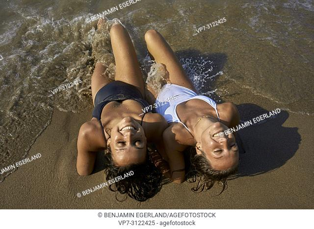 Two young women relaxing on beach. Chersonissos, Crete, Greece
