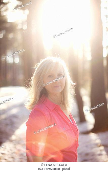Portrait of mature woman in sunlit forest