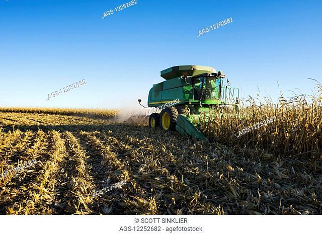A farmer harvests yellow grain corn with his John Deere combine in Southern Iowa; Iowa, United States of America