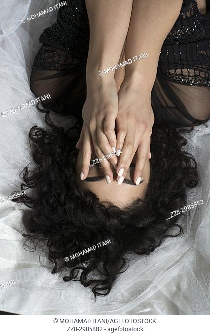 young woman laying down in bed hands covering face