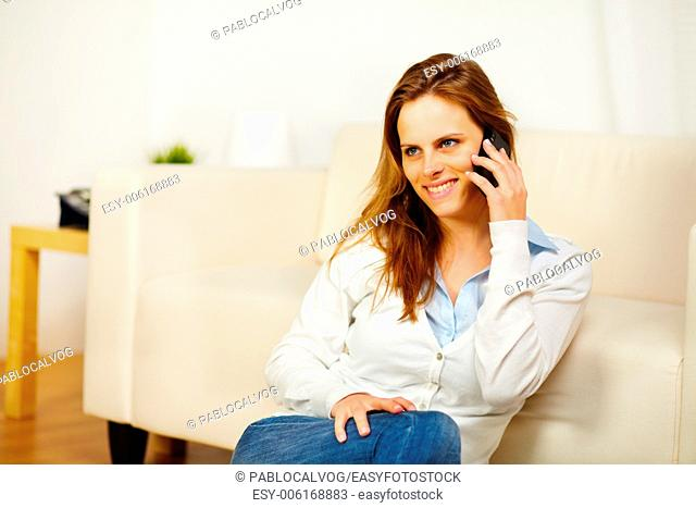 Portrait of a young friendly woman having fun on mobile phone