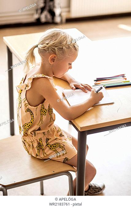 Side view of girl drawing at desk in classroom