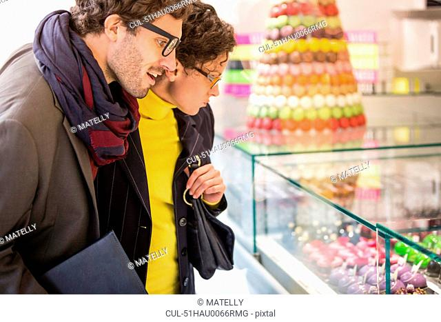 Couple admiring pastries in case