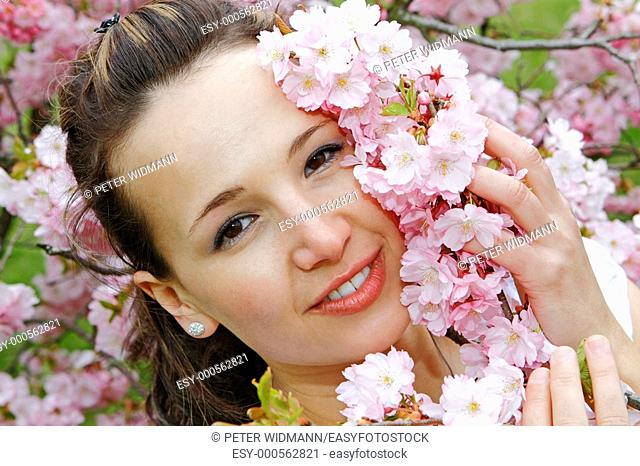 Happy young woman in the spring, blooming cherry tree, cherry blossoms