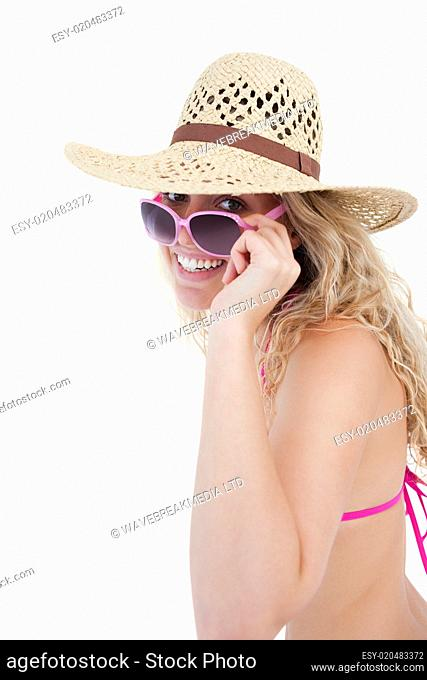 Smiling teenager in a swimsuit looking over her sunglasses
