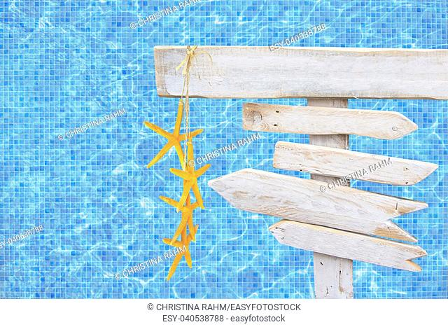White rustic wood arrow signs with yellow starfish over turquoise blue mosaic pool water surface summer theme travel vacation background
