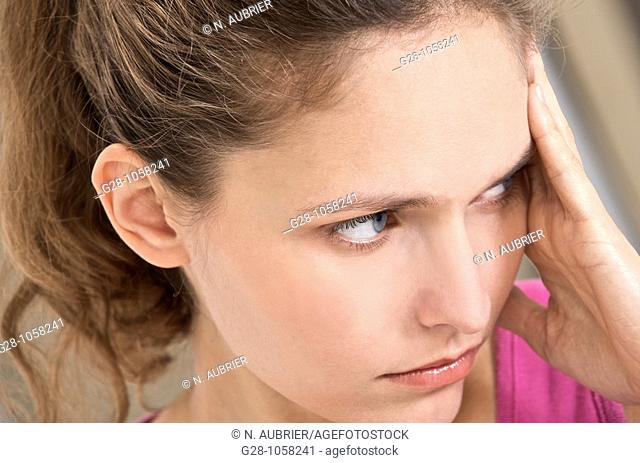 young woman holding her forehead suffering from a headache
