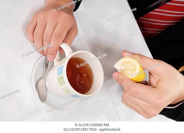 Businessman squeezing lemon into tea