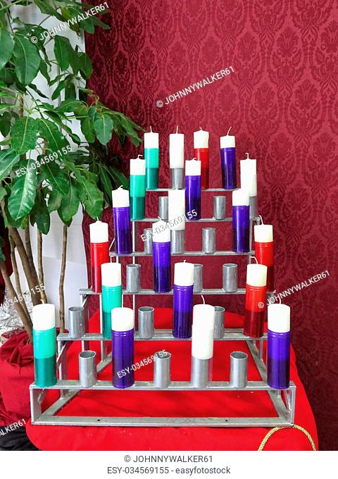 Group of white votive candles in multicoloured plastic candle holders