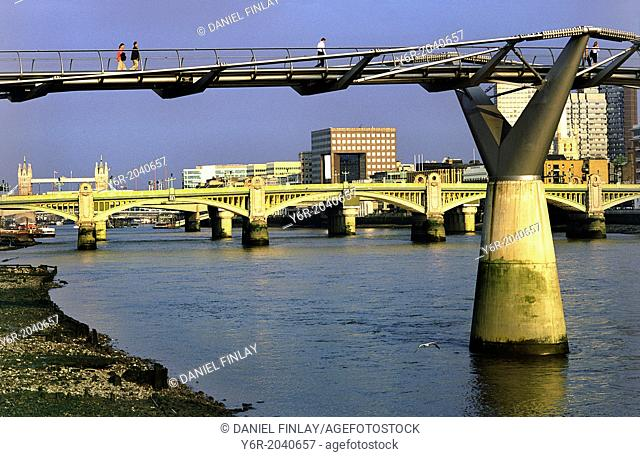 The Millennium Footbridge across the River Thames in the heart of London, England, at low tide, on a sunny Sunday