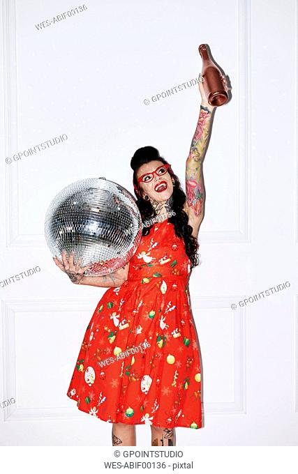 Portrait of tattooed woman with champagne bottle and disco ball