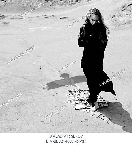 Caucasian teenage girl standing on beach near shadow of eagle