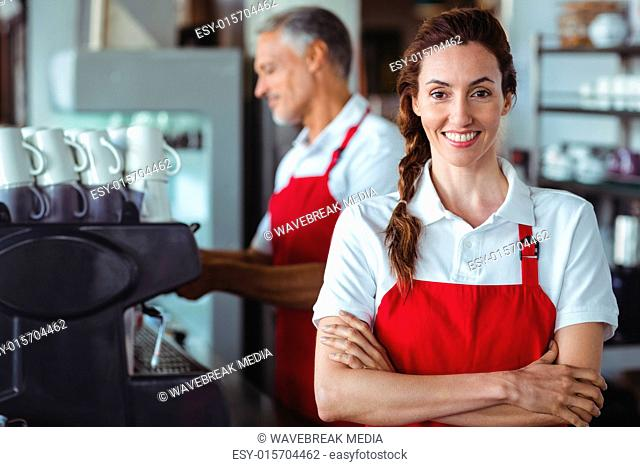 Pretty barista smiling at camera with colleague behind