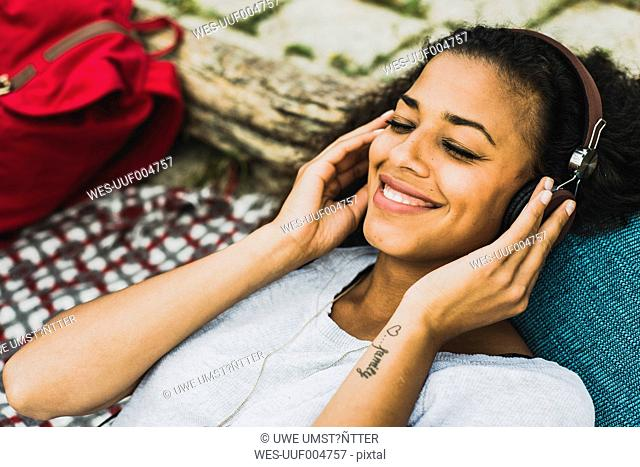 Smiling young woman with headphones outdoors