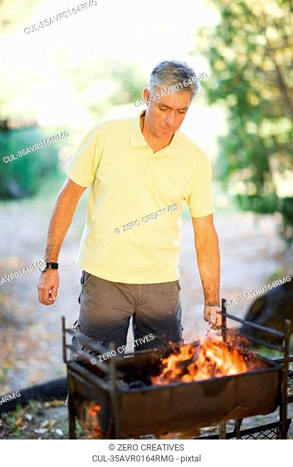 Man firing up barbecue grill