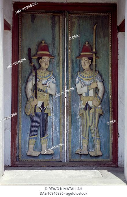 The swinging doors of the Audience Hall (Dusit Maha Prasad) with depictions of soldiers in colonial European uniforms, Grand Palace, Bangkok. Thailand