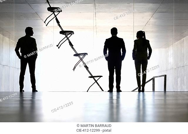 Business people standing next to office chair installation art