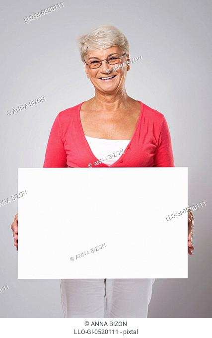 Lovely senior woman covering by whiteboard. Debica, Poland