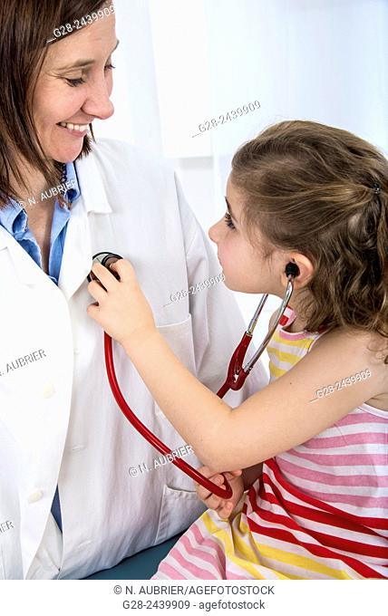 Little girl in doctor's surgery, auscultating the woman doctor with her stethoscope