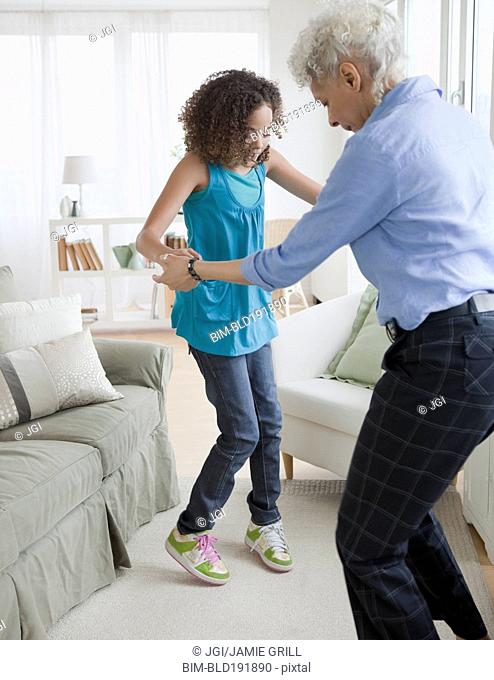 Grandmother and granddaughter dancing in living room