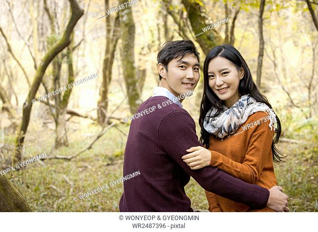 Side view portrait of young smiling couple hugging staring at front in forest