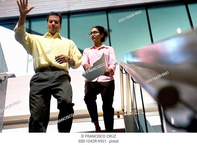 Low angle view of a businessman and a businesswoman walking down stairs