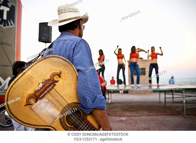Street musician watching female dancers during celebrations around San Felipe Baja 250 off road race, San Felipe, Mexico