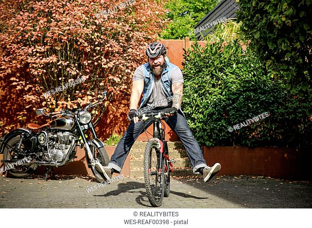 Portrait of happy man switching from motorbike to bicycle