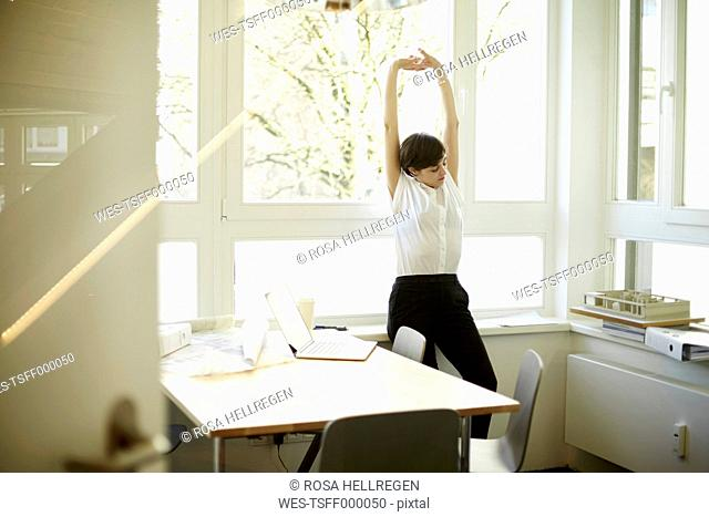 Woman doing stretching exercise in her office
