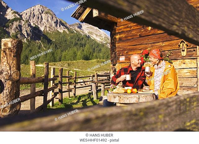 Couple sitting in front of alpine hut
