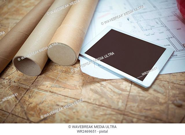 Digital tablet and blueprint on a table at workshop